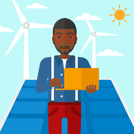 cartoon wind: An african-american man holding a laptop in hands on a background with solar pannels and wind turbins vector flat design illustration. Square layout. Illustration