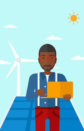 cartoon business: An african-american man holding a laptop in hands on a background with solar pannels and wind turbins vector flat design illustration. Vertical layout.