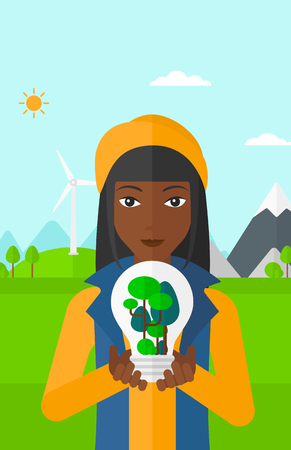 An african-american woman standing on a background with wind turbins and holding in hands a big lightbulb with trees inside vector flat design illustration. Vertical layout. Vettoriali