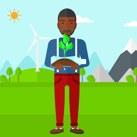 green environment: An african-american man standing on a background with wind turbins and holding in hands a plastic bottle with a small plant growing inside vector flat design illustration. Square layout.