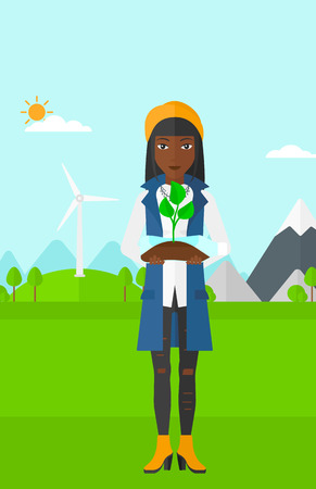 An african-american woman standing on a background with wind turbins and holding in hands a plastic bottle with a small plant growing inside vector flat design illustration. Vertical layout.