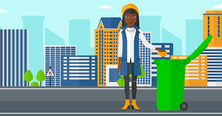 An african-american woman throwing a trash into a green bin on a city background vector flat design illustration. Horizontal layout.