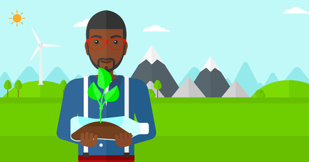 small plant: An african-american  man standing on a background with wind turbins and holding in hands a plastic bottle with a small plant growing inside vector flat design illustration. Horizontal layout.