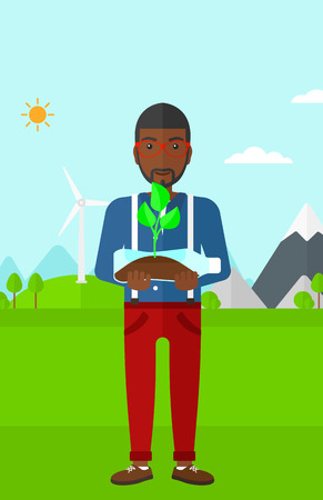 environment protection: An african-american man standing on a background with wind turbins and holding in hands a plastic bottle with a small plant growing inside vector flat design illustration. Vertical layout. Illustration