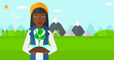 small plant: An african-american woman standing on a background with wind turbins and holding in hands a plastic bottle with a small plant growing inside vector flat design illustration. Horizontal layout.