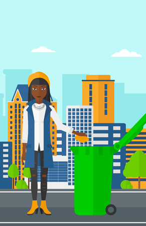 An african-american woman throwing a trash into a green bin on a city background vector flat design illustration. Vertical layout. Vettoriali