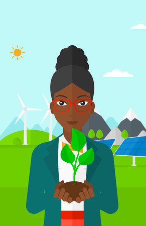 hands holding plant: An african-american woman holding in hands a small plant in soil on a background with solar pannels and wind turbins vector flat design illustration. Vertical layout.