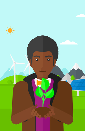 hands holding plant: An african-american man holding in hands a small plant in soil on a background with solar pannels and wind turbins vector flat design illustration. Vertical layout.