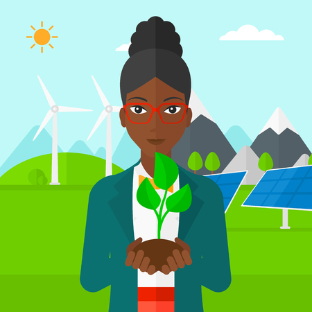hands holding plant: An african-american woman holding in hands a small plant in soil on a background with solar pannels and wind turbins vector flat design illustration. Square layout. Illustration