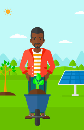 planted: An african-american man standing with a plant and soil in a wheelbarrow on a background with newly planted trees and solar panels vector flat design illustration. Vertical layout. Illustration