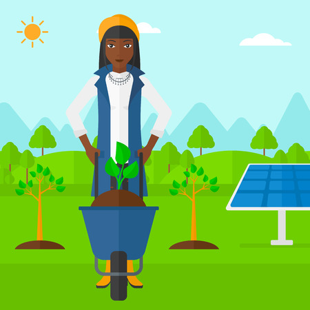 An african-american woman standing with a plant and soil in a wheelbarrow on a background with newly planted trees and solar panels vector flat design illustration. Square layout. Illustration