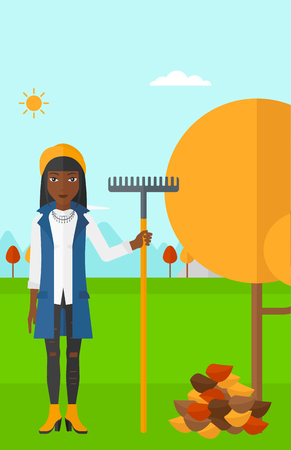 autumn woman: An african-american woman with rake standing near tree and heap of autumn leaves vector flat design illustration. Vertical layout.