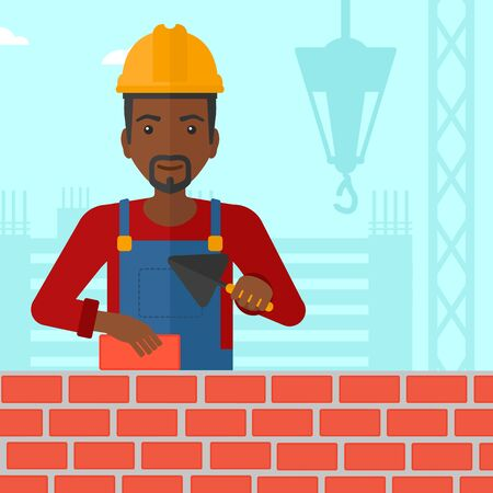 bricklayer: An african-american bricklayer with a spatula and a brick in hands on a background of construction site vector flat design illustration. Square layout.