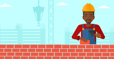 bricklayer: An african-american bricklayer with a spatula and a brick in hands on a background of construction site vector flat design illustration. Horizontal layout. Illustration