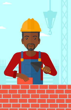 brick and mortar: An african-american bricklayer with a spatula and a brick in hands on a background of construction site vector flat design illustration. Vertical layout.