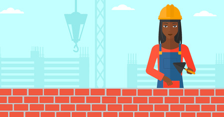 brick and mortar: An african-american female bricklayer with a spatula and a brick in hands on a background of construction site vector flat design illustration. Horizontal layout. Illustration