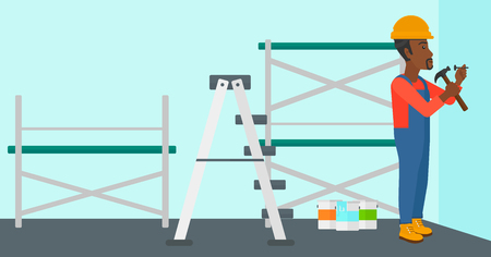 An african-american man hitting a nail in the wall with a hummer on a background of room with paint cans and ladder vector flat design illustration. Horizontal layout.