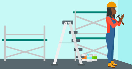 paint cans: An african-american woman hitting a nail in the wall with a hummer on a background of room with paint cans and ladder vector flat design illustration. Horizontal layout. Illustration