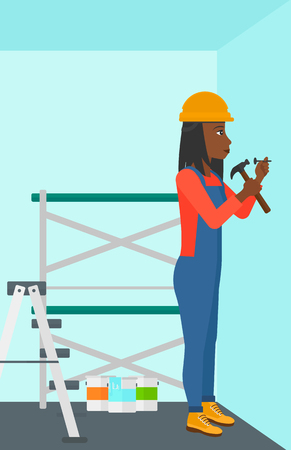 An african-american woman hitting a nail in the wall with a hummer on a background of room with paint cans and ladder vector flat design illustration. Vertical layout.