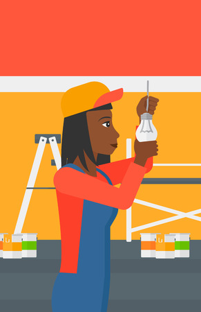 mounting: An african-american female worker twisting a light bulb on a background of room with paint cans and ladder vector flat design illustration isolated on white background. Vertical layout.