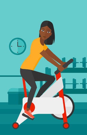 stationary bicycle: An african-american woman exercising on stationary training bicycle in the gym vector flat design illustration. Vertical layout. Illustration