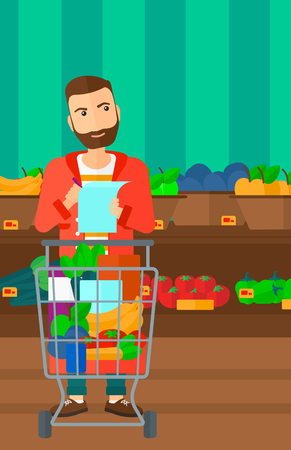A thoughtful hipster man with the beard standing with full supermarket trolley and holding a shopping list in hands on the background of shelves with vegetables and fruits in supermarket vector flat design illustration. Vertical layout.
