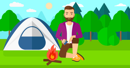 kindling: A hipster man with the beard kindling a fire on the background of camping site with tent vector flat design illustration. Horizontal layout.