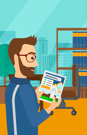 A hipster man with the beard standing in modern office with city view and looking at house on digital tablet screen vector flat design illustration. Vertical layout. Çizim