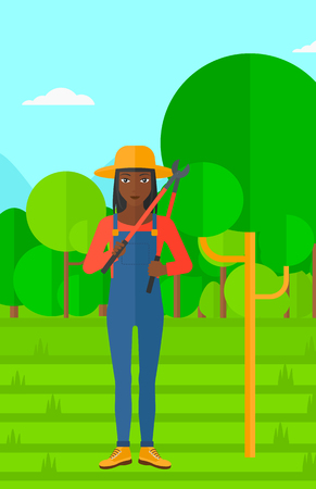 vertical garden: An african-american woman holding a pruner on a background of garden with trees vector flat design illustration. Vertical layout. Illustration