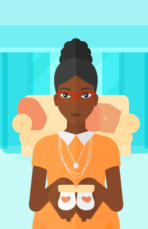 An african-american pregnant woman holding baby booties in hands on the background of living room vector flat design illustration. Vertical layout. Ilustrace