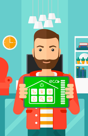 A hipster man with the beard holding a tablet computer with smart home application on a screen on the background of modern  living room vector flat design illustration. Vertical layout. Illusztráció