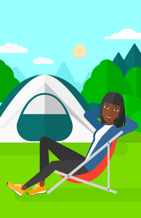 backgrounds trees: An african-american woman sitting in a folding chair on the background of camping site with tent vector flat design illustration. Vertical layout.