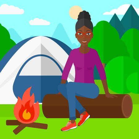 An african-american woman sitting on a log near the fire on the background of camping site with tent vector flat design illustration. Square layout.