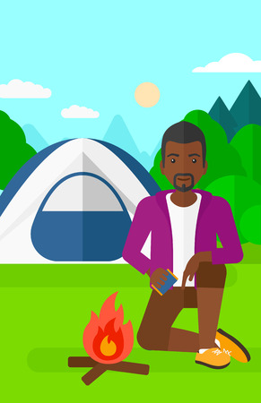 kindle: An african-american man kindling a fire on the background of camping site with tent vector flat design illustration. Vertical layout. Illustration