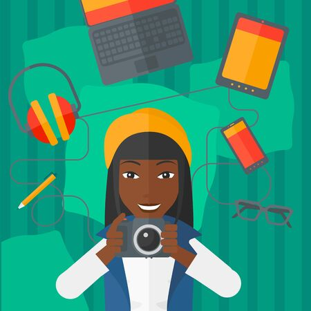 multiple ethnicities: An african-american woman holding a camera on a green background with gadgets vector flat design illustration. Square layout.