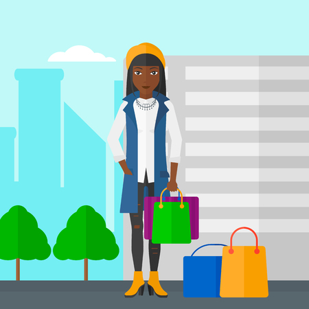 An african-american woman standing with some shopping bags in hand and some bags on the ground on a city background vector flat design illustration. Square layout. Illustration