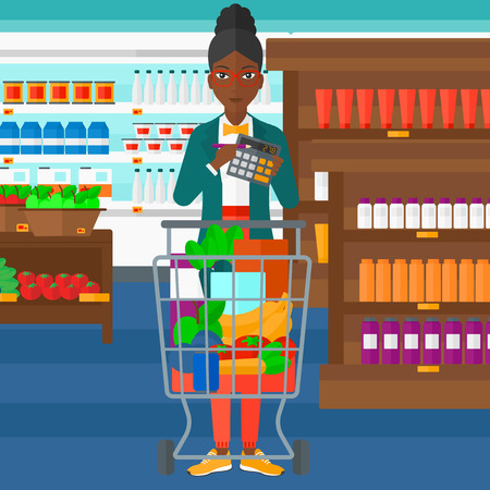 woman shopping cart: An african-american woman standing near shopping cart and holding a calculator in hands on the background of supermarket shelves with products vector flat design illustration. Square layout.