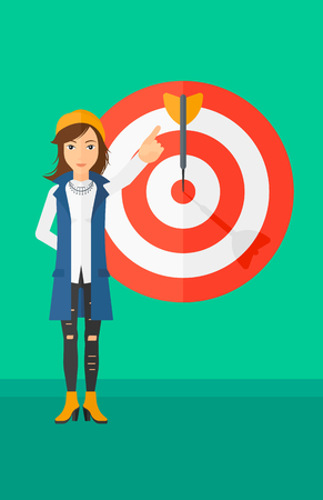 A woman pointing at arrow in a target board on a green background vector flat design illustration. Vertical layout. Иллюстрация