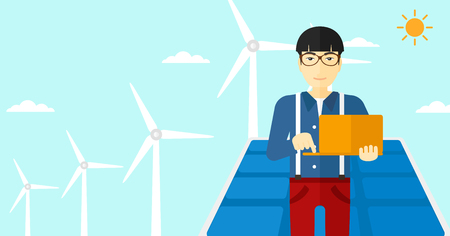 An asian man holding a laptop in hands on a background with solar pannels and wind turbins vector flat design illustration. Horizontal layout.