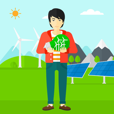 An asian man standing on a background with solar pannels and wind turbins and holding in hands a big light bulb with small wind turbines inside vector flat design illustration. Square layout. Ilustrace
