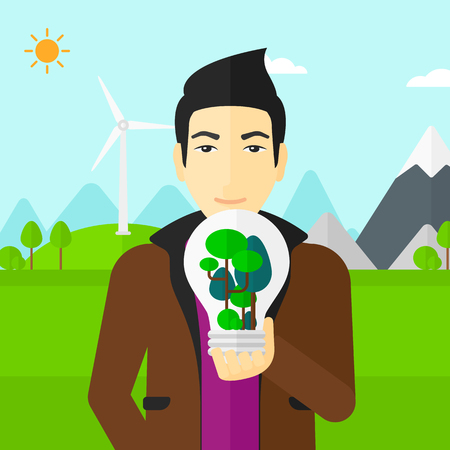 An asian man standing on a background with wind turbins and holding in hands a big lightbulb with trees inside vector flat design illustration. Square layout. Vettoriali