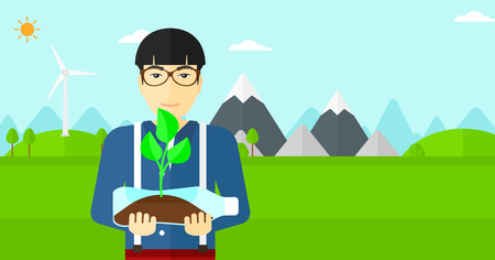 An asian man standing on a background with wind turbins and holding in hands a plastic bottle with a small plant growing inside vector flat design illustration. Horizontal layout. Vettoriali