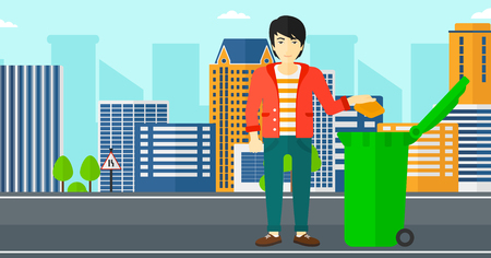 An asian man throwing a trash into a green bin on a city background vector flat design illustration. Horizontal layout. Иллюстрация