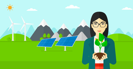 hands holding plant: An asian woman holding in hands a small plant in soil on a background with solar pannels and wind turbins vector flat design illustration. Horizontal layout. Illustration