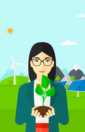 small plant: An asian woman holding in hands a small plant in soil on a background with solar pannels and wind turbins vector flat design illustration. Vertical layout.