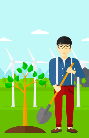 An asian man with the shovel plants a tree on a background with wind turbins vector flat design illustration. Vertical layout. Vettoriali