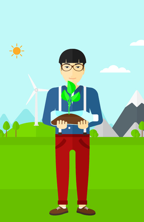 An asian man standing on a background with wind turbins and holding in hands a plastic bottle with a small plant growing inside vector flat design illustration. Vertical layout.