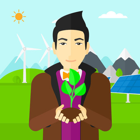 hands holding plant: An asian man holding in hands a small plant in soil on a background with solar pannels and wind turbins vector flat design illustration. Square layout.