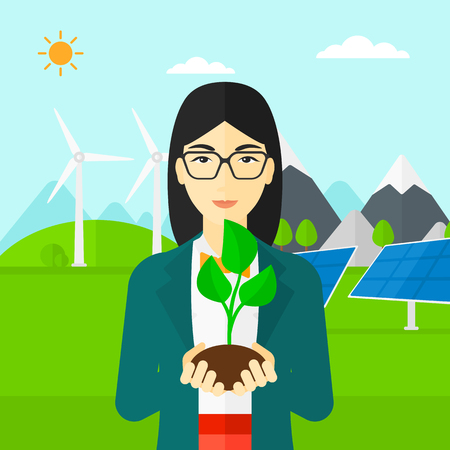 hands holding plant: An asian woman holding in hands a small plant in soil on a background with solar pannels and wind turbins vector flat design illustration. Square layout. Illustration