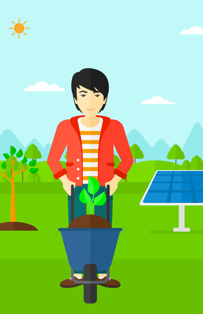 An asian man standing with a plant and soil in a wheelbarrow on a background with newly planted trees and solar panels vector flat design illustration. Vertical layout.